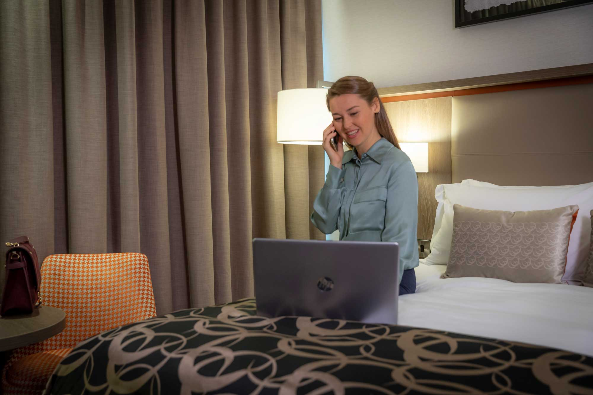 female guest working in her clayton hotels bedroom